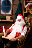Santa Claus in Workshop With List. Santa Claus sitting in his workshop making notes on his naughty list with a quill pen. Vertical Composition Royalty Free Stock Images