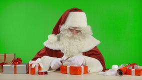 Santa Claus is Wrapping a Gift with Red Colored Paper stock video