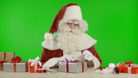 Santa Claus is Wrapping a Gift with Silver Colored Paper stock video footage