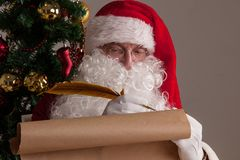 Santa Claus writing on old paper. Santa Claus sitting at home and writing on old paper roll to do list with quill pen and ink Royalty Free Stock Photography