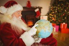 Santa Claus wskazuje jego palcowego na kuli ziemskiej Zdjęcie Royalty Free