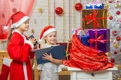 Santa Claus y el ayudante cuentan de nuevo los regalos en un bolso Fotos de archivo