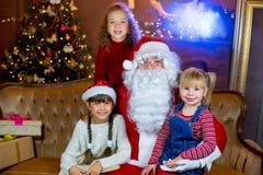 Santa Claus y grupo de muchachas que leen un libro Fotografía de archivo libre de regalías