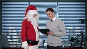 Santa Claus y hombre de negocios joven en una oficina moderna, cantidad común almacen de metraje de vídeo