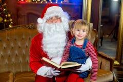 Santa Claus y muchachas que leen un libro Imagen de archivo libre de regalías