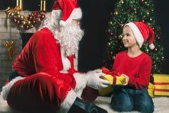 Santa Claus y muchacho felices cerca del árbol de navidad adornado Fotografía de archivo libre de regalías