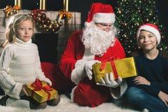 Santa Claus y niños felices alrededor del árbol de navidad adornado Imágenes de archivo libres de regalías
