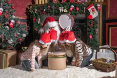 Santa Claus y niños que abren presentes en la chimenea imagen de archivo