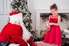 Santa Claus y niños que abren presentes en la chimenea Los niños engendran en regalos abiertos de la Navidad de la barba del traj Fotografía de archivo libre de regalías