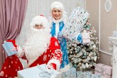 Santa Claus y nieta con los regalos del Año Nuevo en sus manos ` S del Año Nuevo y la Navidad Imagen de archivo libre de regalías