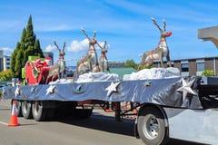 Santa Claus y señora Santa y su montar a caballo del reno en un flotador del desfile de la Navidad imagen de archivo