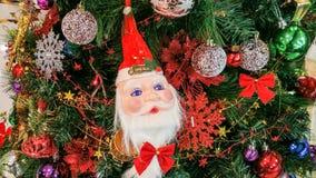 Santa Claus y un x27; cara de s en un árbol de navidad Imagen de archivo libre de regalías