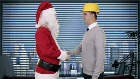 Santa Claus and Young Architect in a modern office, shaking hands and looking at camera, stock footage Royalty Free Stock Photos