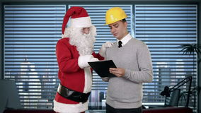 Santa Claus and Young Architect in a modern office, stock footage Stock Photo