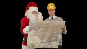 Santa Claus with a Young Architect reading a map, against black, stock footage stock video footage