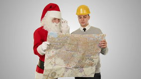 Santa Claus with a Young Architect reading a map, against white, stock footage stock video