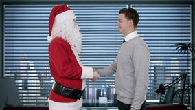 Santa Claus and Young Businessman in a modern office, shaking hands and looking at camera, stock footage Royalty Free Stock Photo