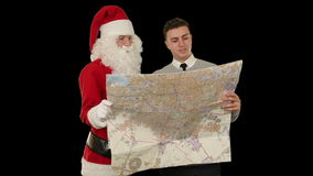 Santa Claus with a Young Businessman reading a map, against black, stock footage stock footage