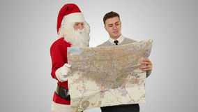 Santa Claus with a Young Businessman reading a map, against white, stock footage stock video footage