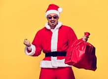 Santa Claus. Young Happy Santa Man Winner Gesture. Handsome Fashion guy, Christmas Santa sack bag, Presents Having Fun. New Year. Emotional Sporty Confident Royalty Free Stock Photo