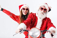 Santa Claus And Young Mrs Claus Riding A de Motorfiets stock afbeeldingen