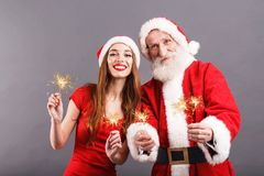 Santa Claus And Young Mrs Claus Standing With Sparklers On Gray Background stock foto's