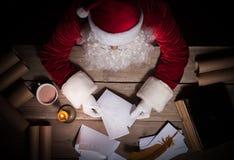 Santa Claus-zitting bij de lijst in zijn ruimte en het openen Kerstmisbrief van kind stock foto's