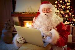 Santa Claus-zitting door de open haard met laptop royalty-vrije stock afbeeldingen
