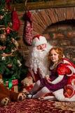 Santa Claus-zitting met een klein meisje royalty-vrije stock afbeelding