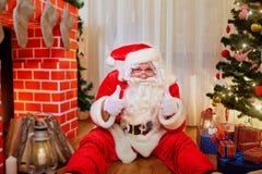 Santa Claus-zitting op de vloer die zijn duim in roo tegenhouden royalty-vrije stock foto's