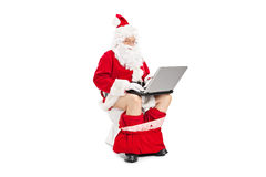 Santa Claus-zitting op een toilet en het werken met laptop Stock Foto's