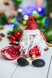 Santa Claus-zitting op een witte houten lijst aangaande een achtergrond van groene slingers en Kerstmislichten Stock Fotografie