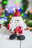Santa Claus-zitting op een witte houten lijst aangaande een achtergrond van groene slingers en Kerstmislichten Royalty-vrije Stock Foto's