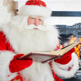 Santa Clause. Santa sitting at the Christmas tree, fireplace and reading a book stock photography