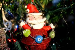 JOY-ful Santa Christmas tree ornament. Santa Clause bell ornament with merry eyes and bearded smile holds a garland of J O Y on the Christmas tree with lights stock images