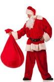 Santa Clause carrying a heavy sack Stock Photos