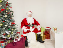 Santa Clause on the chair in holiday scene. Man in Santa Claus outfit is sitting in the middle of the image with hands on his knees. on the left side of the Royalty Free Stock Image