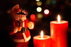 Santa Clause And Christmas Lights. Santa Clause with lamp, two red burning candlse and colorful bokeh in the background Royalty Free Stock Photography