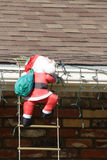 Santa Clause Climbing. A latter up on to a roof Royalty Free Stock Photo