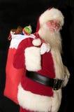 Santa Clause Delivering Presents. Color photograph of Santa Clause delivering presents against a black cloth background Royalty Free Stock Photo