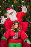 Santa Clause with elf helper Xmas armchair Stock Images