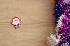 A Santa Clause figurine with tinsel. A Santa Clause figurine with purple, blue and white tinsel Royalty Free Stock Image