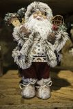 Santa-clause frosty model decoration boots clothes smile cheeks. Santa clause model figurine adorned with winter fur clothes with snowshoes and a birdhouse royalty free stock photography