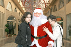 Santa Clause and girls. Santa Clause and two pretty girls in shopping centre Stock Image