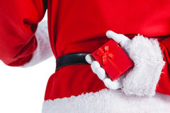 Santa clause holding a gift box behind his back Stock Images