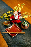Santa Clause Japanese Style. Antique Buddha Statue with Candles and Flowers Royalty Free Stock Photos
