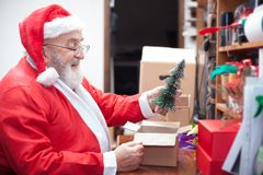 Santa Clause packing a gift Stock Images