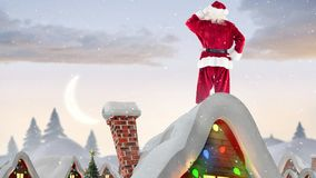 Santa clause on a roof of a decorated house in winter scenery combined with falling snow