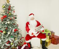 Santa Clause on the chair in holiday scene. Santa Clause Sitting on the chair in the middle of the image and looking into the book. on the left side of the image Royalty Free Stock Photo