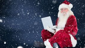 Santa clause sitting in front of his laptop combined with falling snow. Digital composite of Santa clause sitting in front of his laptop combined with falling stock video footage